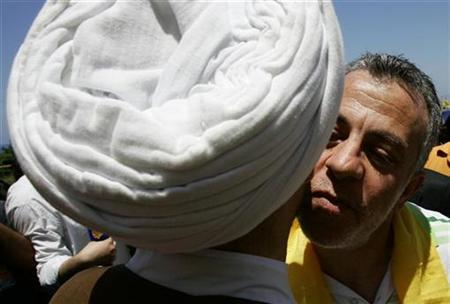 Nissim Nasser (R) kisses Hezbollah senior official Sheikh Nabil Qawouk upon his arrival at Naqoura village in south Lebanon June 1, 2008. Lebanese should stop greeting each other with kisses to the cheek, Health Minister Mohammad Khalifeh told a news conference on Tuesday called to explain measures to tackle the potential spread of the deadly strain. REUTERS/Ali Hashisho