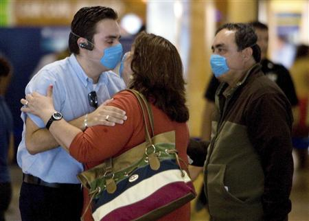 A couple wearing surgical masks kiss each other goodbye as the woman is about to board a plane at the international airport in Cancun, Mexico in this file photo from April 27, 2009. REUTERS/Victor Ruiz
