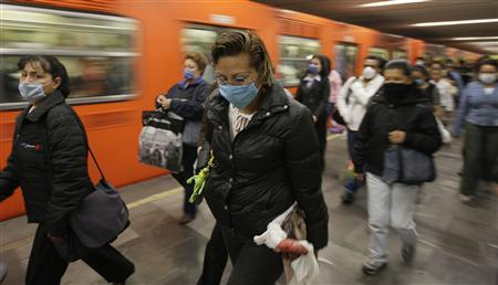 Passengers wear protective masks at Mexico's city subway April 28, 2009. The World Health Organisation said on Tuesday it was possible the current outbreak of swine flu around the world could be a mild pandemic but warned the 1918 Spanish flu, which killed millions, started mildly. REUTERS/Daniel Aguilar