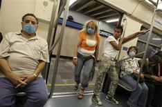<p>Commuters wear protective masks in a subway in Mexico City April 29, 2009. A deadly swine flu outbreak could push Mexico deeper into recession, hurting an economy that shrank by as much as 8 percent in the first quarter, Mexico's central bank said on Wednesday. REUTERS/Daniel Aguilar</p>