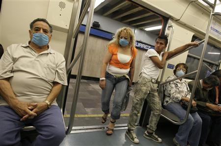 Commuters wear protective masks in a subway in Mexico City April 29, 2009. A deadly swine flu outbreak could push Mexico deeper into recession, hurting an economy that shrank by as much as 8 percent in the first quarter, Mexico's central bank said on Wednesday. REUTERS/Daniel Aguilar