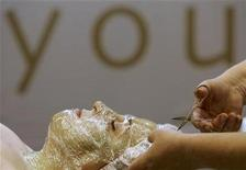 <p>A woman has her face covered with a plastic mask while receiving a facial treatment at a beauty fair in Bucharest in this file photo from March 1, 2007. REUTERS/Bogdan Cristel</p>