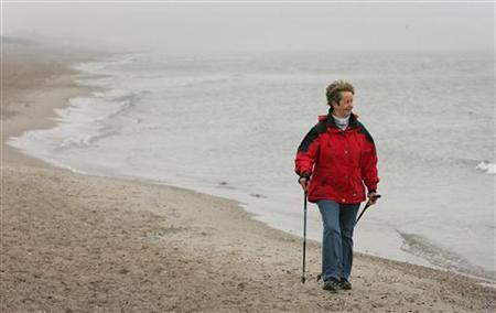 An elderly woman practices Nordic walking for rehabilitation exercise on the beach outside at a clinic in Damp on Germany's Baltic sea coast April 13, 2006. REUTERS/Christian Charisius