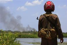 <p>A Sri Lankan government soldier looks across to a trail of smoke coming from inside the 'No Fire Zone' near the town of Putumatalan located in northern Sri Lanka in this April 24, 2009 file photo. REUTERS/David Gray/Files</p>