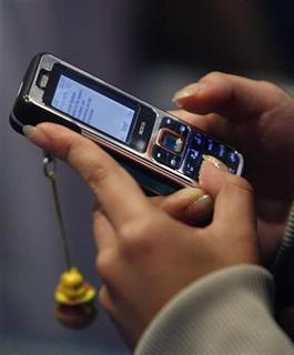A competitor types a text message into a mobile phone during a competition in Singapore November 12, 2006. REUTERS/Vivek Prakash