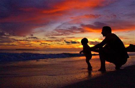 A father plays with his son during sunrise at Kailua Beach in Hawaii, October 19, 2003. REUTERS/Lucy Pemoni