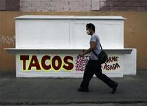 <p>Un uomo con la mascherina chirurgica passa davanti a un chiosco di tacos chiuso a Città del Messico. REUTERS/Eliana Aponte</p>