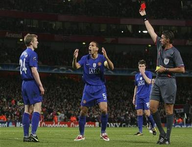 Darren Fletcher (L) of Manchester United is shown the red card by referee Roberto Rosetti as team mate Rio Ferdinand (C) reacts during their Champions League second leg semi-final soccer match against Arsenal at the Emirates stadium in London May 5, 2009. REUTERS/Stringer