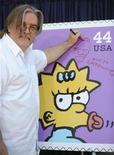 """<p>El creador y productor ejecutivo Matt Groening firma un afiche durante la develación de las nuevas estampillas de """"The Simpsons"""" en Los Angeles, may 7 2009. REUTERS/Phil McCarten</p>"""