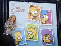 """<p>Симпсона, стоит рядом с постером, на котором изображены почтовые марки с главными героями мультсериала, в Лос-Анджелесе 7 мая 2009 года. """"Симпсоны"""" - самая любимая """"ненормальная"""" семья Америки, у которой в четверг появились свои собственные почтовые марки. REUTERS/Phil McCarten</p>"""