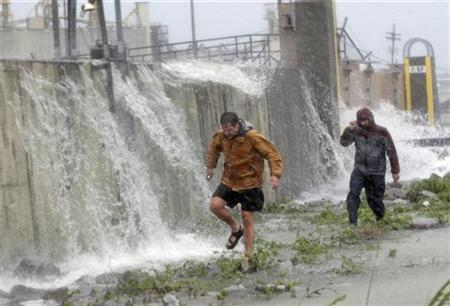 People walk along the Industrial Canal flood wall in the Ninth Ward in New Orleans after the center of Hurricane Gustav came ashore, September 1, 2008. REUTERS/Dave Martin