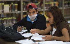 <p>A student wears a surgical mask inside a library at Instituto Politechnico Nacional University after it was reopened, in Mexico City May 7, 2009. Millions of high school and university students returned to classes in Mexico as the government said the worst of the flu crisis is over and the country got back on its feet after shutting public places last week to avoid spread of the virus. REUTERS/Jorge Dan</p>