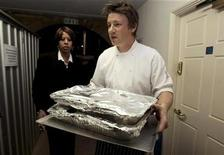 <p>Celebrity chef Jamie Oliver (C) carries out food for a G20 leaders dinner at Downing Street in London April 1, 2009. REUTERS/Christopher Furlong/Pool</p>