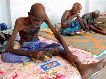 Tamil men who said they are more than 100 years old eat their food rations at a temporary shelter in the Samanagkulam school located on the outskirts of the town of Vavuniya in northern Sri Lanka May 11, 2009. REUTERS/Stringer