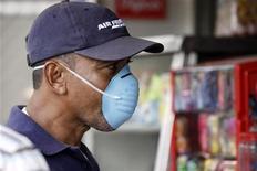 """<p>Человек защищается от вируса свиного гриппа с помощью маски. Финляндия во вторник официально подтвердила два случая заражения вирусом гриппа A/H1N1, известного также как """"свиной"""". REUTERS/Alberto Lowe</p>"""
