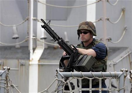 A U.S sailor stands on guard on the deck of the warship Bainbridge guard upon arrival at the port of Mombasa, 500km from the capital Nairobi, April 16, 2009. REUTERS/Antony Njuguna