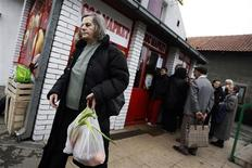 <p>A woman leaves from a government-backed social SOS discount supermarket in Belgrade March 31, 2009. REUTERS/Marko Djurica</p>