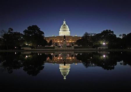 The United States Capitol Building is reflected in the water at sunrise in Washington, October 31, 2008. REUTERS/Jim Young
