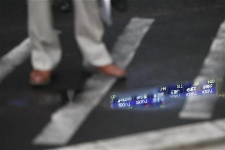 A stock quotation board is reflected on a puddle as a man waits at a traffic crossing in Tokyo April 14, 2009. REUTERS/Issei Kato