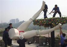 """<p>Рабочие демонтируют скульптуру, стоявшую на входе в тематический парк """"Страна Любви"""" в городе Чунцин 16 мая 2009 года. Тематический парк """"Страна любви"""" был закрыт властями Китая за несколько месяцев до открытия, вызвав гнев чиновников, сообщила газета China Daily. REUTERS/China Daily</p>"""