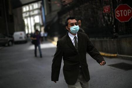 A man wears a medical mask while walking in lower Manhattan in New York, April 29, 2009. REUTERS/Eric Thayer