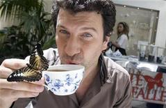<p>Event organiser Fabio di Gioia drinks a cup of tea while accompanied by a Silvia butterfly, in the aviary of Galleria Borghese in Rome May 13, 2009. REUTERS/Chris Helgren</p>