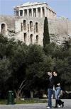 <p>Una pareja camina cerca del Acrópolis en Atenas, 27 feb 2009. Grecia abrirá en junio un nuevo Museo de la Acrópolis, dijo el miércoles su ministro de Cultura, con el propósito de recuperar obras históricas que ahora se exponen en el Museo Británico de Londres. REUTERS/Yiorgos Karahalis</p>