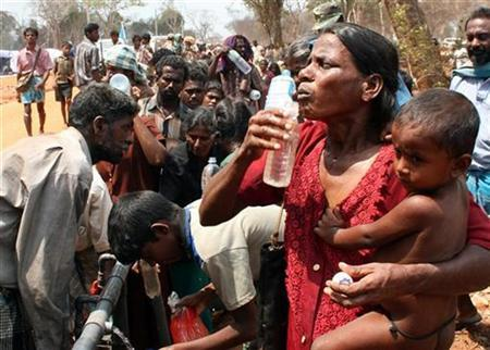 Refugees who fled the area held by the Liberation Tigers of Tamil Eelam stand in a line to receive food and water in a refugee camp located near the town of Manik in northern Sri Lanka April 26, 2009. REUTERS/Stringer