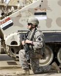 <p>Американский солдат охраняет танк иракской армии в пригороде Багдада 12 апреля 2009 года. Сенат США в четверг одобрил законопроект о выделении $91,3 миллиарда на военные действия в Афганистане и Ираке. REUTERS/Saad Shalash</p>