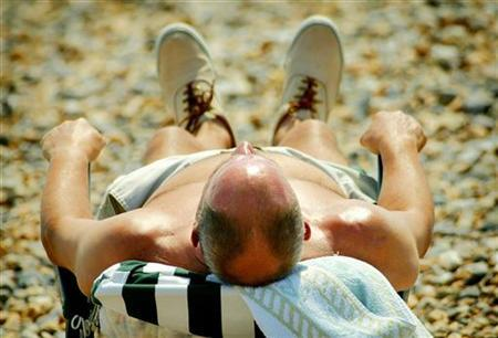 A sunbather enjoys the heatwave in Britain's southern coastal town of Worthing, July 15, 2003. REUTERS/Peter Macdiarmid