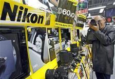 <p>Un hombre prueba una cámara Nikon en una tienda de Tokio, 5 feb 2009. El fabricante japonés de equipos de precisión Nikon dijo el martes que reestructurará su endeudado negocio de conductores en Japón y en el extranjero, recortando 1.000 empleos y conteniendo su búsqueda de más crecimiento a medida que los ingresos se reducen. REUTERS/Yuriko Nakao/Archivo</p>