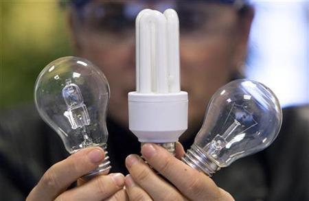An employee shows a traditional light bulb (R) and two low-energy consumption bulbs at the Osram factory in Molsheim, eastern France December 11, 2008. REUTERS/Vincent Kessler