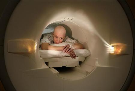 Cancer patient Deborah Charles lies inside the tube of a magnetic resonance imaging scanner during an MRI examination of her breasts at Georgetown University Hospital in Washington May 23, 2007. REUTERS/Jim Bourg