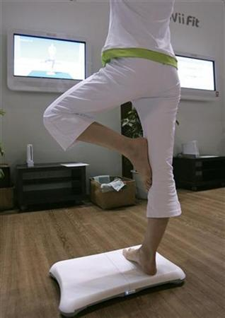 A woman demonstrates Nintendo Co Ltd's ''Wii Fit'' game console during a media event in Chiba, east of Tokyo, October 10, 2007. REUTERS/Yuriko Nakao