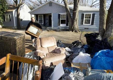 Family belongings are put out on the curb by a worker after McLennan County Deputy Constables delivered a court order of eviction to a family in Waco, Texas, December 31, 2008. REUTERS/Larry Downing