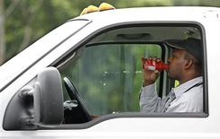 <p>A commuter drinks a beverage as he sits in traffic during morning rush hour into Atlanta, Georgia, May 27, 2009. Driving is a way of life for millions of Americans in cities such as Atlanta which is built for the car, but researchers say they are finding increasing evidence that driving everywhere is bad for your health. REUTERS/Tami Chappell</p>