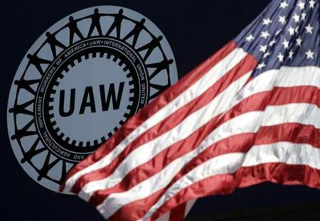 A U.S. flag flutters in the wind in front of the the UAW logo outside the United Auto workers Union Solidarity House in Detroit, Michigan May 29, 2009. REUTERS/Rebecca Cook