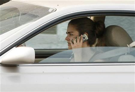 A woman talks on her cell phone while driving in Burbank, California June 25, 2008. Accessing your bank account using your mobile phone might seem safe, but security experts say would-be hackers can access confidential information via a simple text message seemingly from your service provider. REUTERS/Fred Prouser