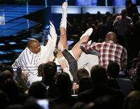 <p>Sacha Baron Cohen, con alas blancas y suspensores, aterriza sobre el rapero Eminem durante los premios MTV en Los Angeles, 31 mayo 2009. El escandaloso aterrizaje del actor Sacha Baron Cohen con las nalgas descubiertas en pleno rostro del músico de rap Eminem durante la entrega de premios MTV fue un truco ensayado, de acuerdo a uno de los guionistas del show. REUTERS/Mario Anzuoni</p>