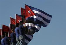 """<p>Члены кубинской молодежной организации держат флаги Кубы во время акции у посольства США в Гаване 12 мая 2009 Организация американских государств (ОАГ) в среду проголосовала за отмену решения об исключении Кубы, принятого в 1962 году в разгар """"холодной войны"""", однако кубинское государственное телевидение поспешило заявить, что Гавана не заинтересована в возвращении в ряды объединения. REUTERS/Enrique De La Osa</p>"""