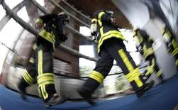 "<p>Firefighters run in Frankfurt's Trade Fair Tower (Messeturm) during the ""skyrun"" in Frankfurt May 24, 2009. REUTERS/Johannes Eisele</p>"