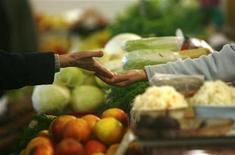<p>A customer pays after buying produce at a market in Riga February 19, 2009. REUTERS/Ints Kalnins</p>