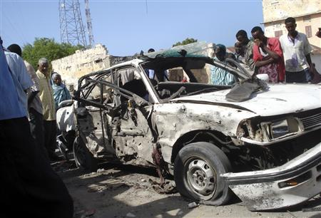 Residents stand around a car destroyed after a bomb exploded on Nasib-Bundo road in Mogadishu June 7, 2009. REUTERS/Mowlid Abdi