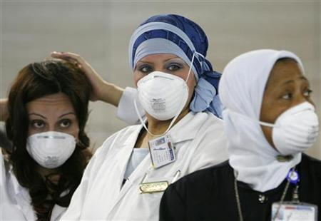 Health worker wearing masks wait to measure the temperature of passengers arriving at Cairo airport, May 14, 2009. REUTERS/Asmaa Waguih