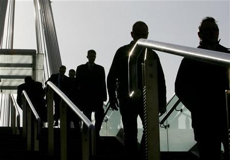 Commuters walk to work over the Golden Jubilee Bridge in central London on April 4, 2006. REUTERS/Toby Melville