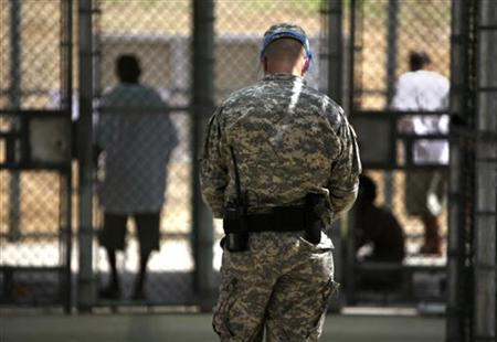 In this photo, reviewed by the U.S. military, and shot through glass, a guard watches over Guantanamo detainees inside the exercise yard at Camp 5 detention facility at Guantanamo Bay U.S. Naval Base, Cuba, May 31, 2009. REUTERS/Brennan Linsley/Pool