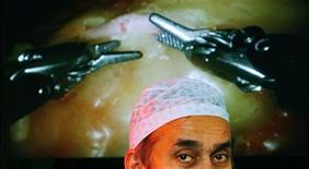 <p>Professor Lord Ara Darzi speaks to Reuters about robotic surgery in front of a streaming video of a robot demonstrating surgery on a prosthetic heart at Imperial College London October 24, 2008. REUTERS/Luke MacGregor</p>
