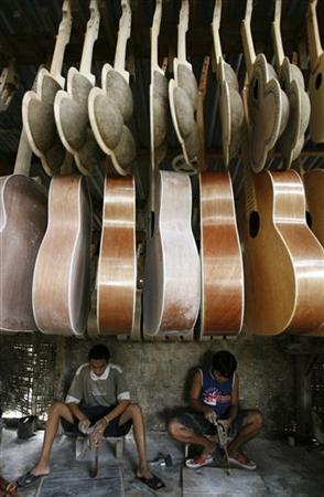 Filipino workers clean ukuleles at a shop in downtown Cebu January 10, 2007. REUTERS/Romeo Ranoco