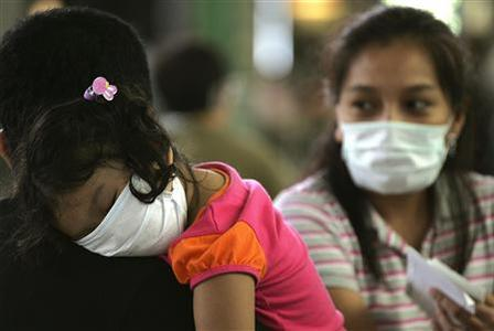 Tourists wear masks as they wait at the airport in Hong Kong June 12, 2009, a day after the World Health Organization (WHO) declared an influenza pandemic and advised governments to prepare for a long-term battle against an unstoppable Influenza A (H1N1) flu virus. REUTERS/Aaron Tam