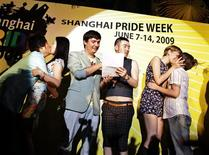 <p>Two gay couples kiss, as part of an unofficial marriage ceremony, during celebrations for mainland China's first Gay Pride week at a bar in Shanghai June 13, 2009. The Gay Pride week celebrations continued in Shanghai despite cancellations of some of the festival's events by city authorities earlier in the week, according to media reports. A fair mix of local and foreign participants took part in the festival. REUTERS/ Nir Elias</p>